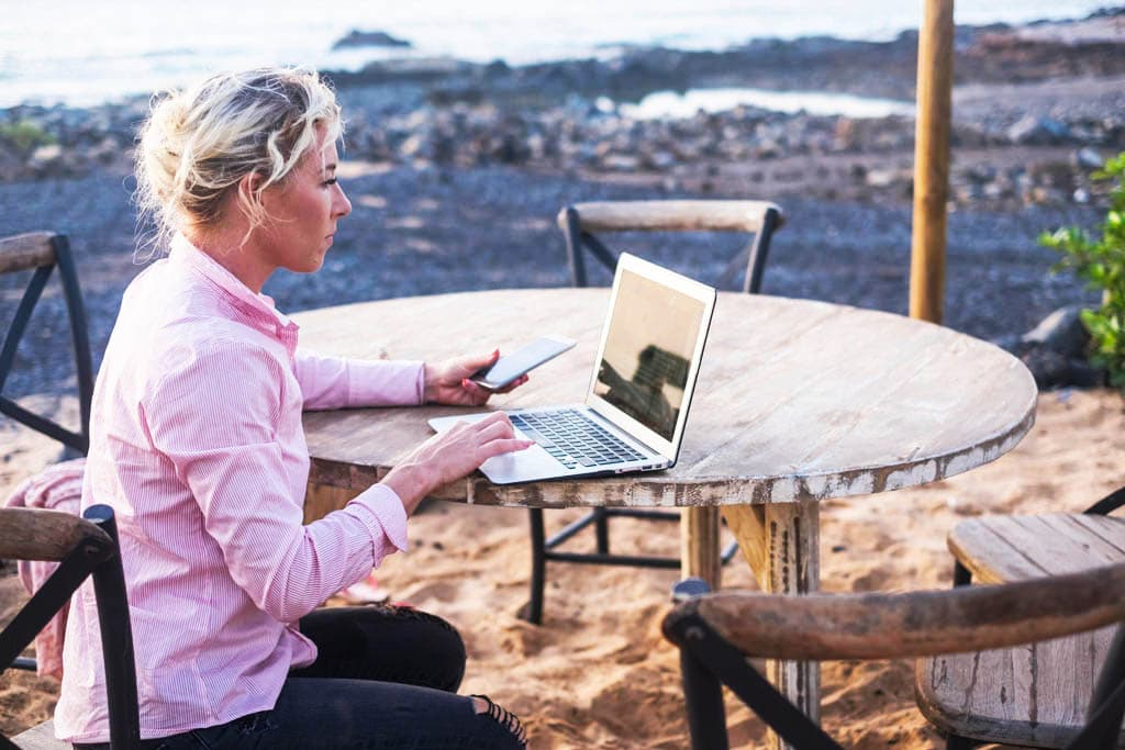 digital nomad concept with blonde free beautiful caucasian middle age woman working at the laptop using cellular phone too sitting on a wood table near the ocean - freelance free to work everywhere with technology